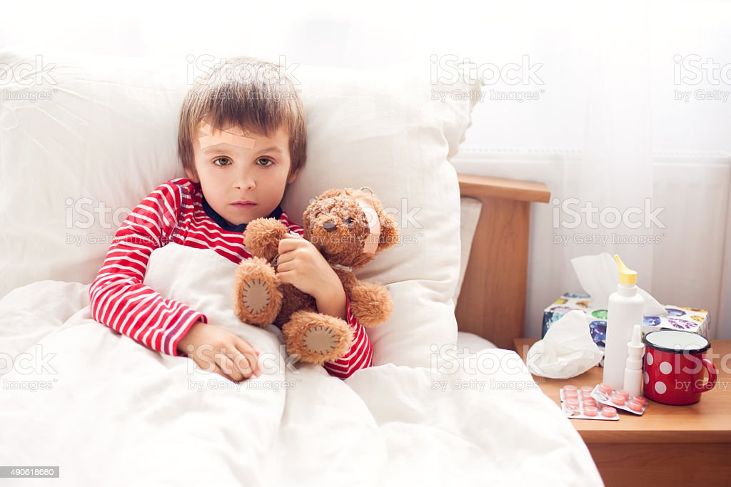 Sick child boy lying in bed with a fever, resting stock photo