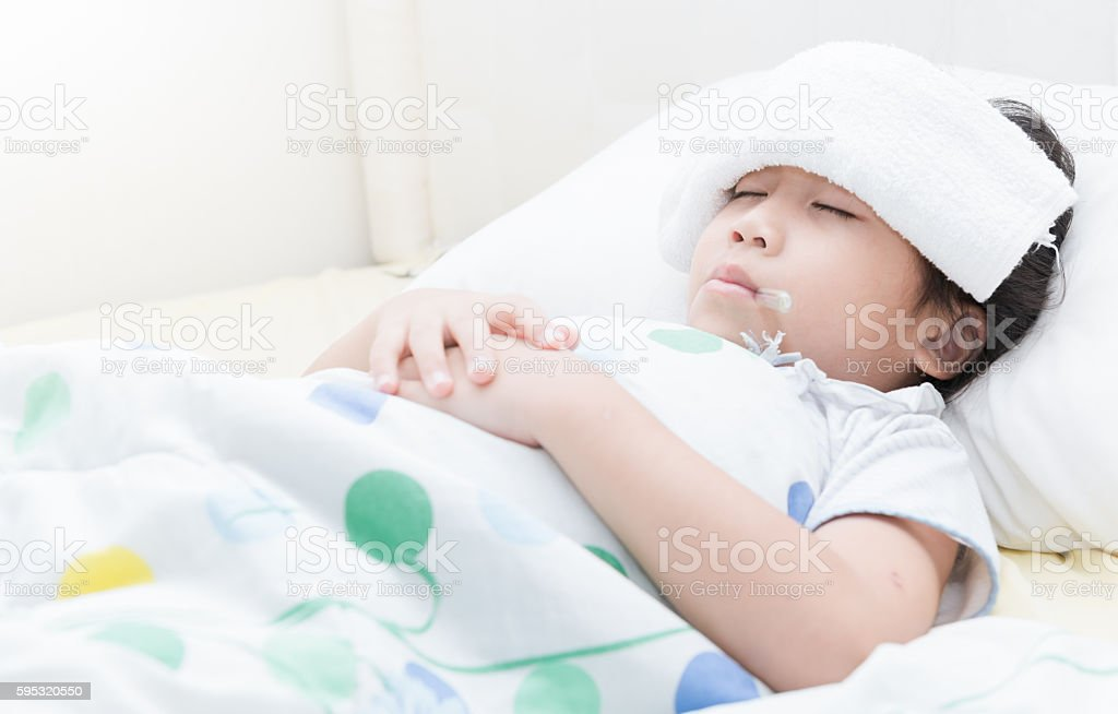 Sick child girl lying in bed stock photo