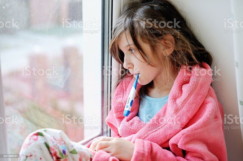 Sick child girl with thermometer in mouth stock photo