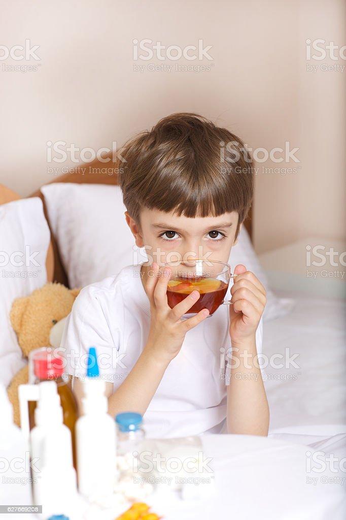 Sick child is drinking tea stock photo
