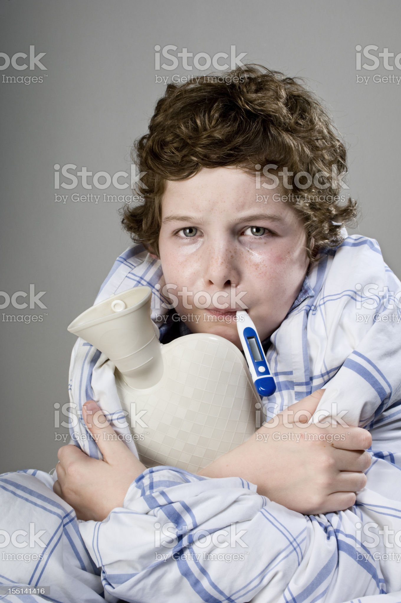 Sick Child With Thermometer Holding a Hot Water Bottle royalty-free stock photo