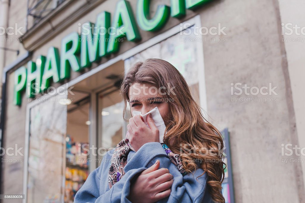 sick cold woman next to a pharmacy, flu concept stock photo