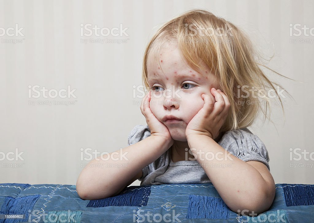 Sick girl is sitting near the bed stock photo