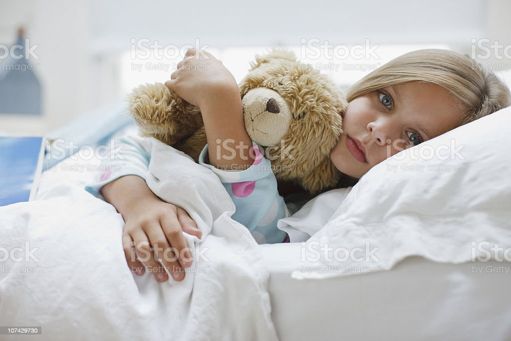 Sick girl laying in bed with teddy bear royalty-free stock photo