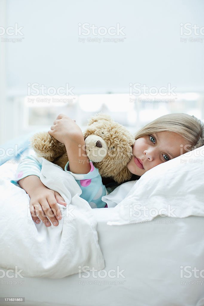 Sick girl laying in bed with teddy bear stock photo