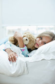 Sick girl laying in bed with teddy bear