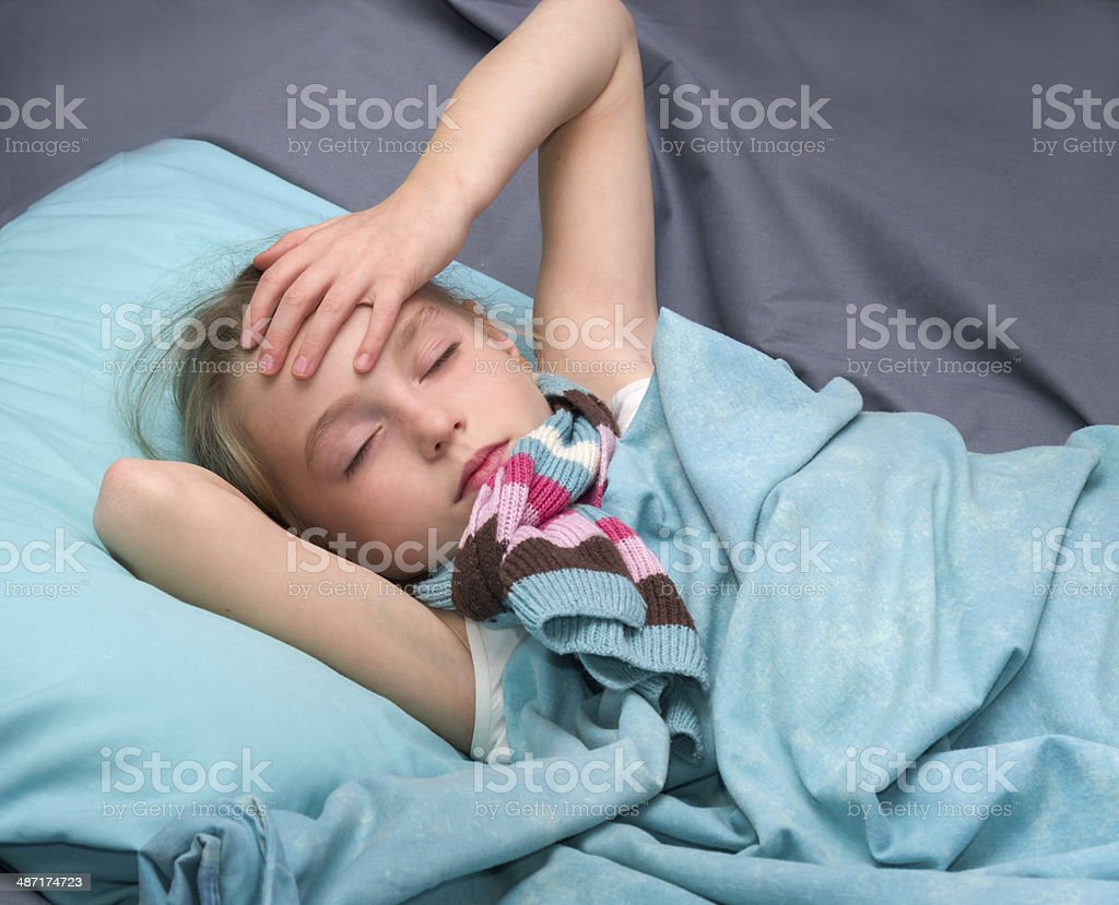 sick girl lying in her bed stock photo