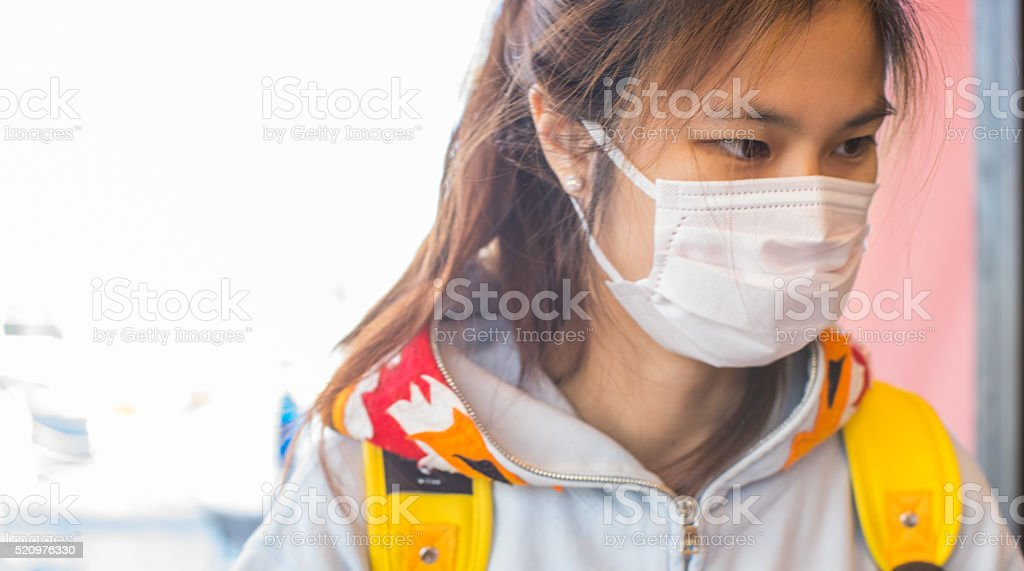 Sick Japanese girl with a mask on stock photo
