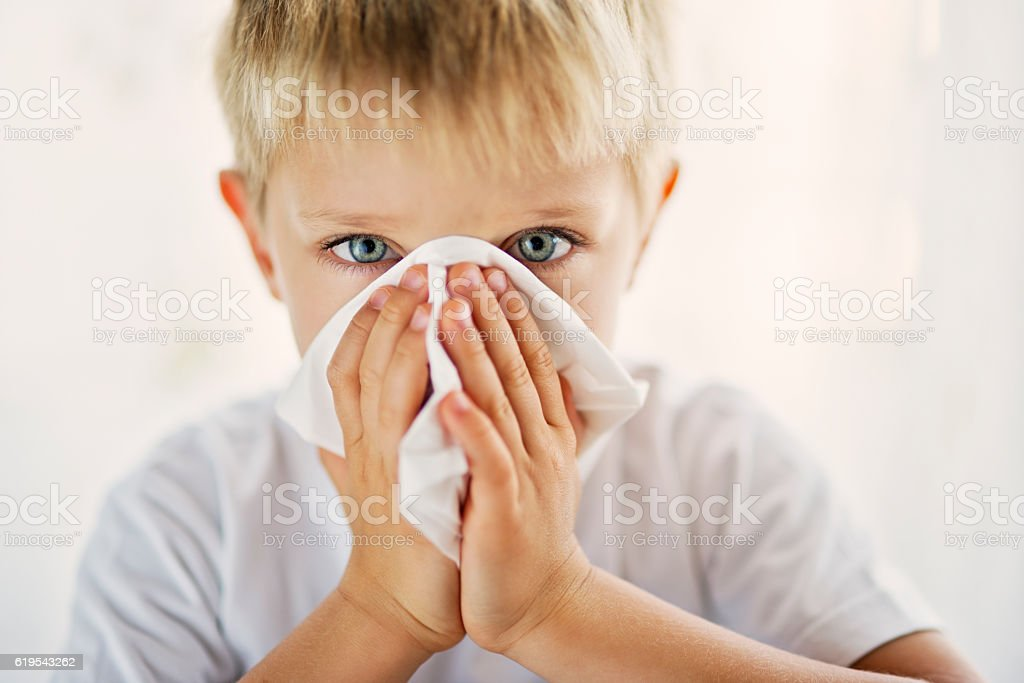 Sick little boy cleaning his runny nose. stock photo