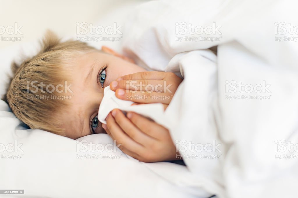 Sick little boy cleaning nose in bed stock photo