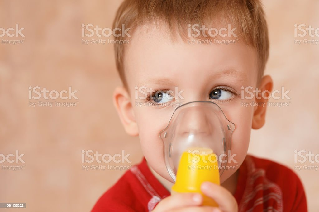 Sick little boy makes inhalation mask for breathing at home stock photo