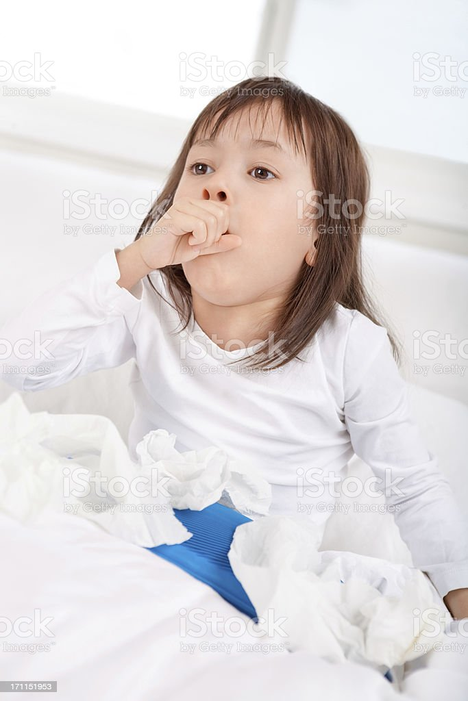 Sick little girl coughing in bed stock photo