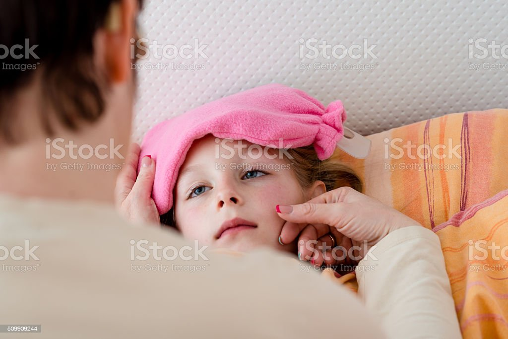 Sick little girl having her body temperature measured stock photo