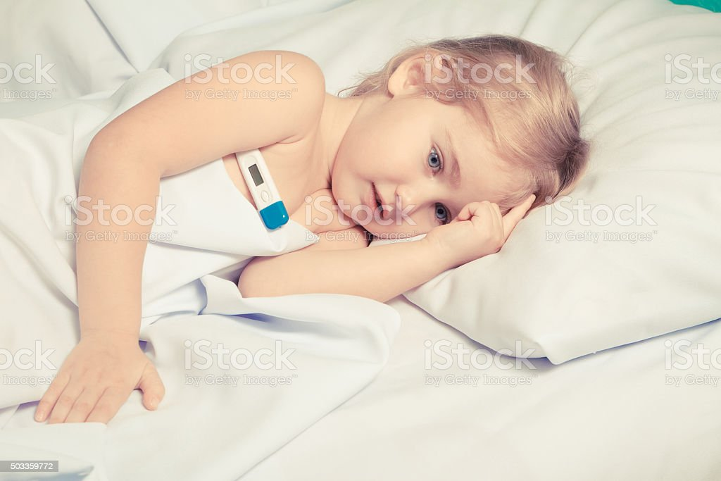 Sick little girl in bed. stock photo