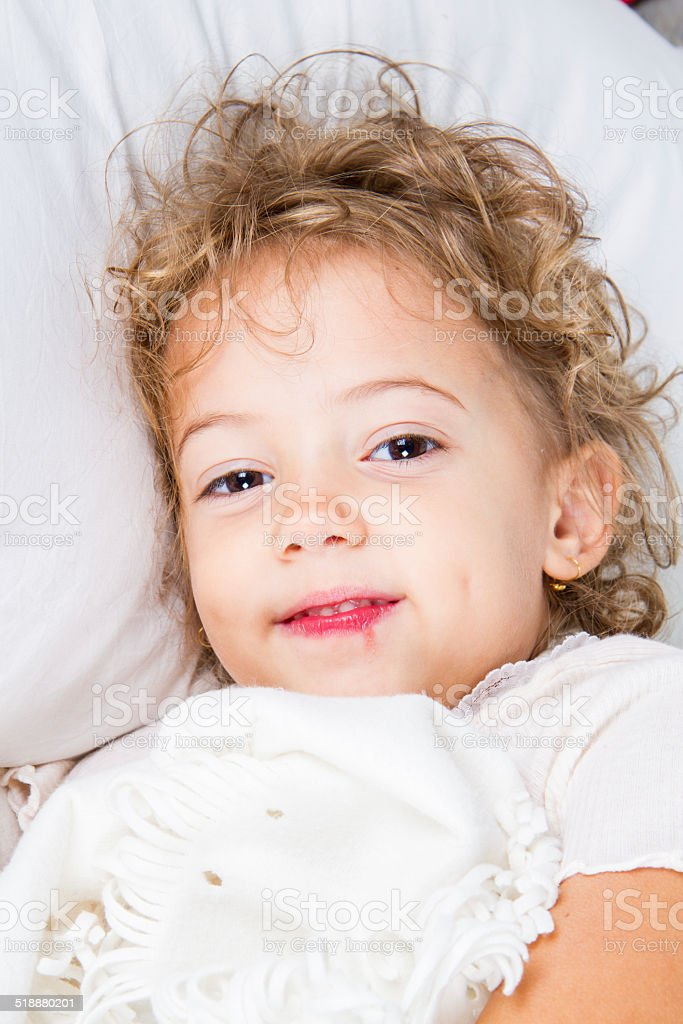 Sick little girl in bed stock photo
