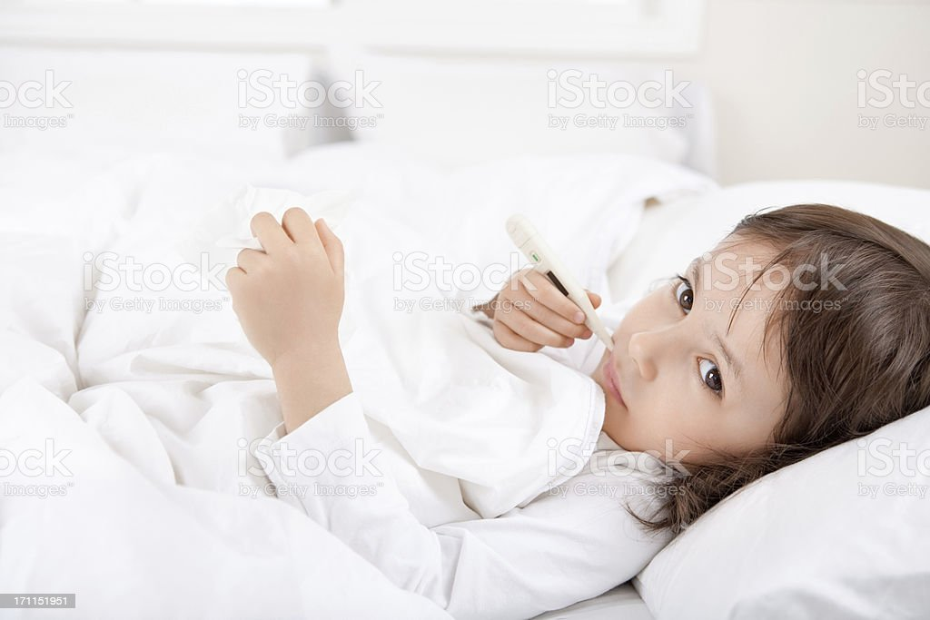 Sick little girl with a thermometer in bed royalty-free stock photo
