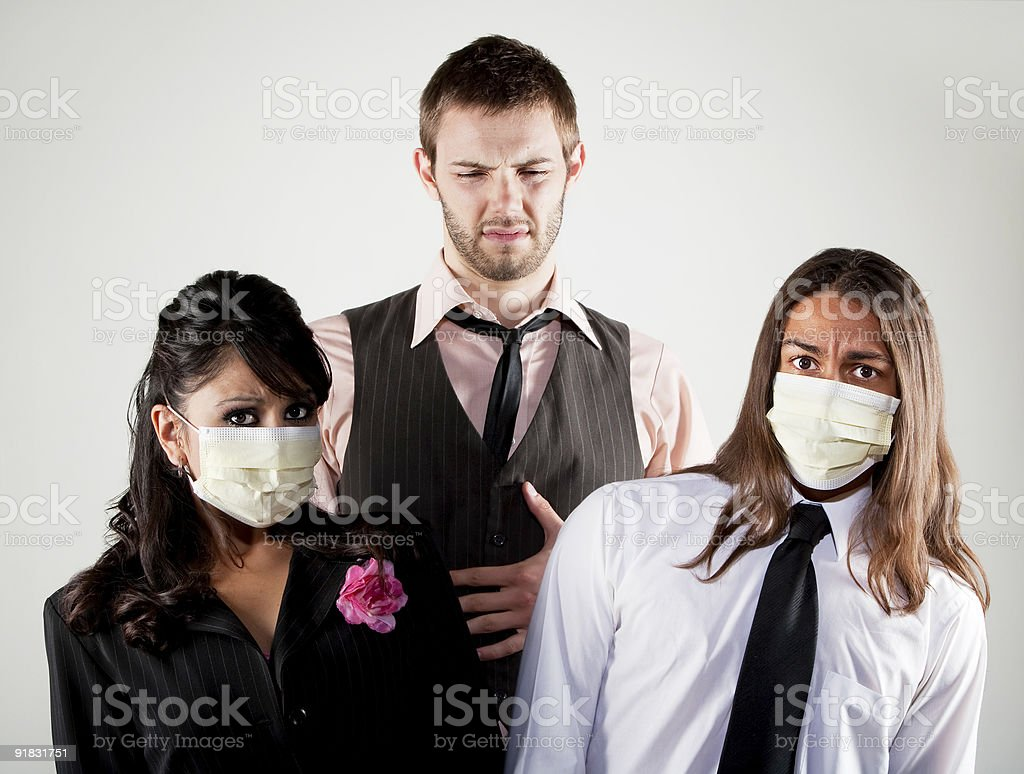 Sick man and worried coworkers in masks royalty-free stock photo