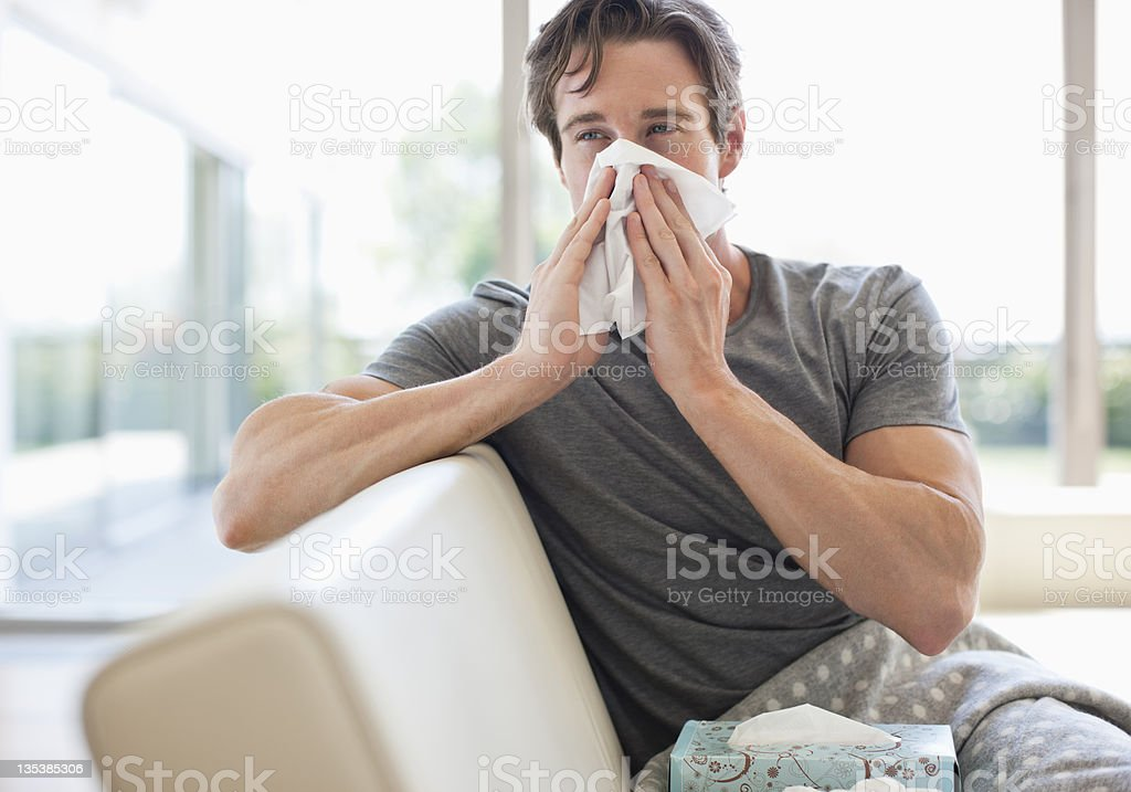 Sick man blowing his nose stock photo
