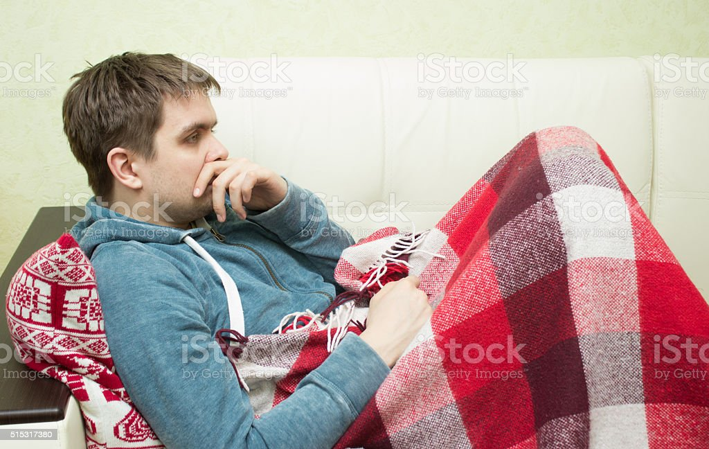 Sick man lying on sofa  at home in living room stock photo