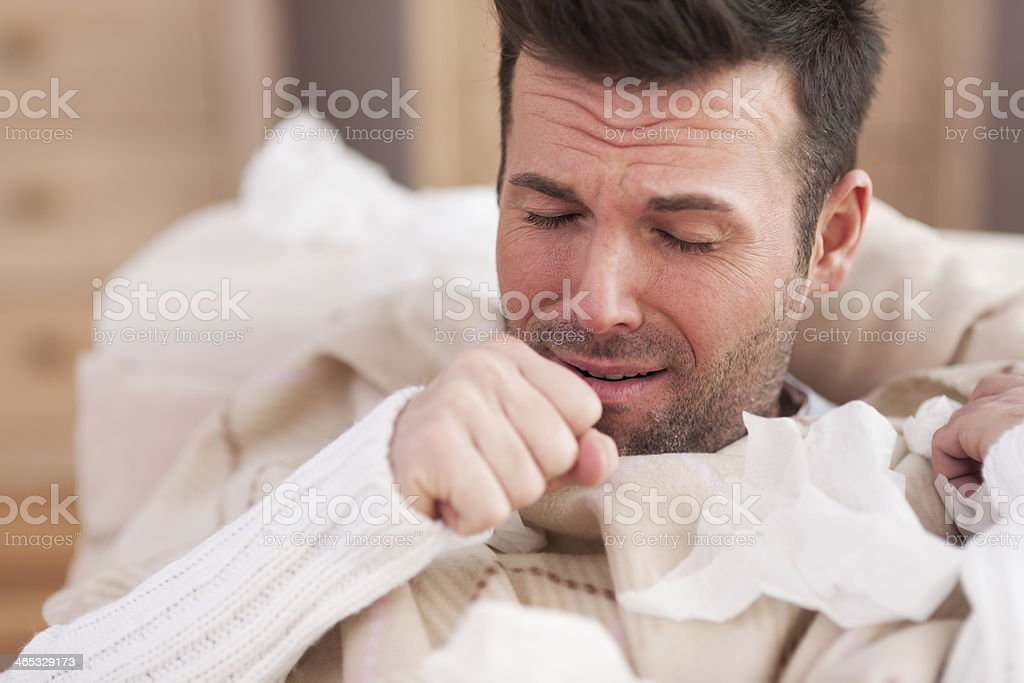 Sick man lying on sofa in living room stock photo