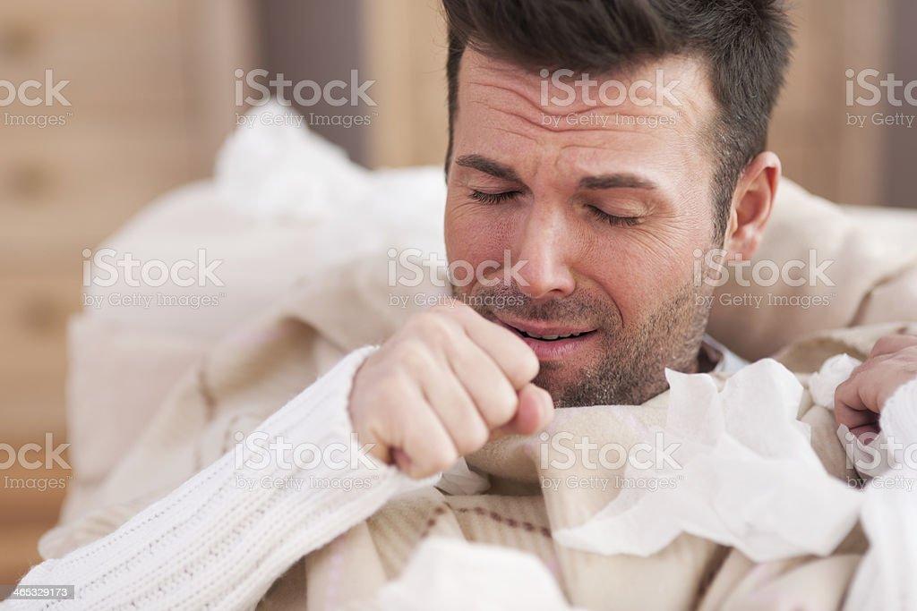 Sick man lying on sofa in living room stock photo