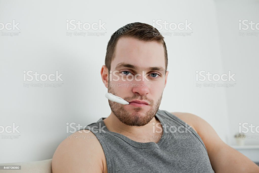 Sick man posing with thermometer stock photo