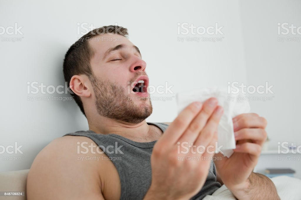 Sick man sneezing stock photo