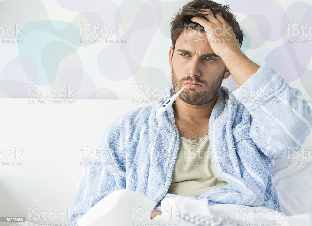 Sick man with thermometer in mouth sitting on bed stock photo