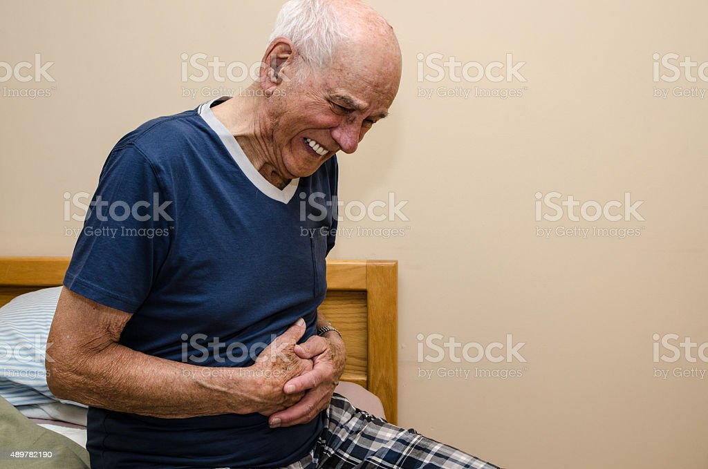 Sick old man holding his stomach suffering stock photo