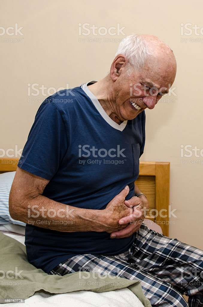Sick old man holding his stomack suffering stock photo