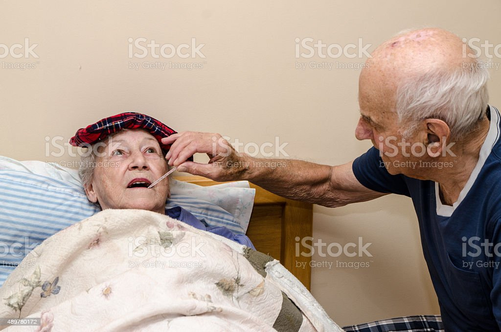 Sick old woman in a bed with temperature being taken stock photo