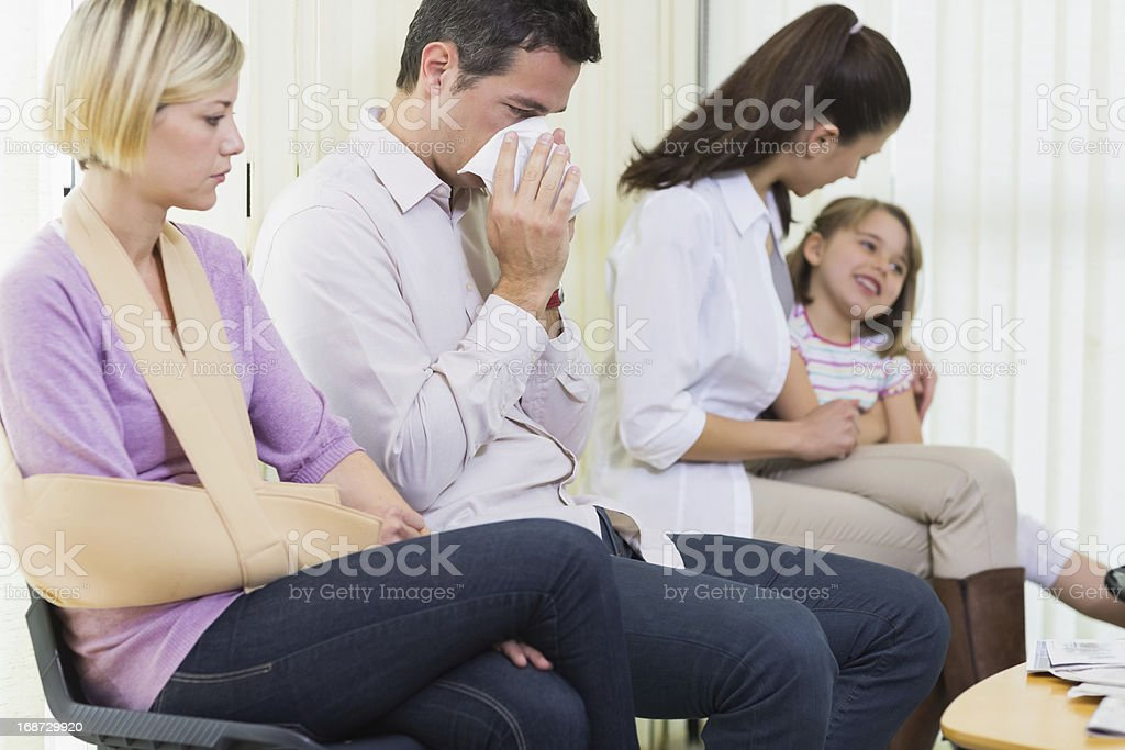 Sick patients sitting in the doctors waiting room stock photo