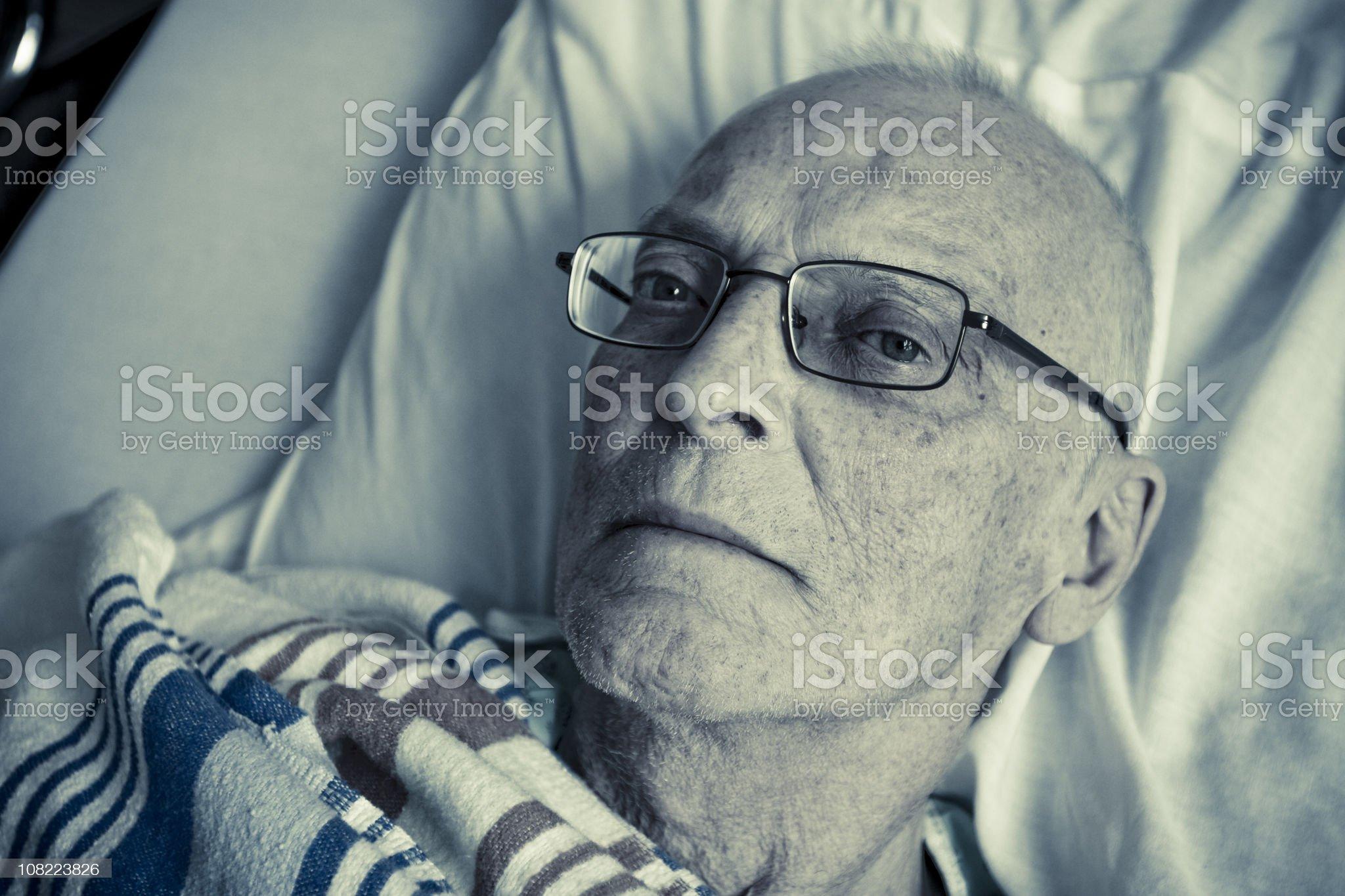 Sick, Senior Man Lying in Hospital Bed royalty-free stock photo