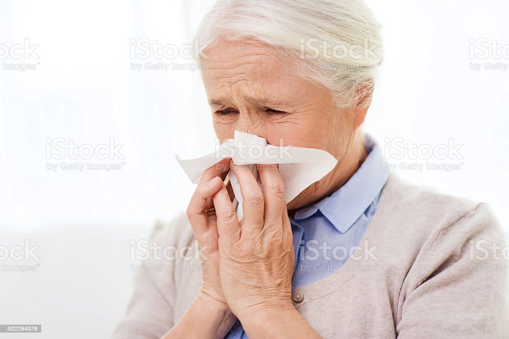 sick senior woman blowing nose to paper napkin stock photo