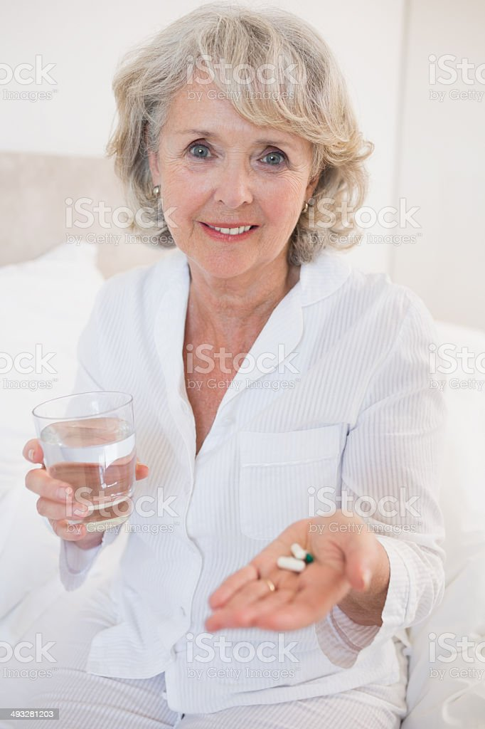 Portrait of a sick senior woman taking her pills with water at home