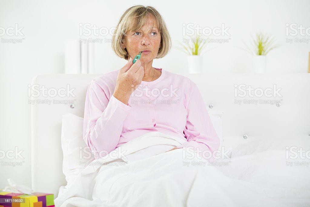 Sick Senior Woman Taking Her Temperature. royalty-free stock photo