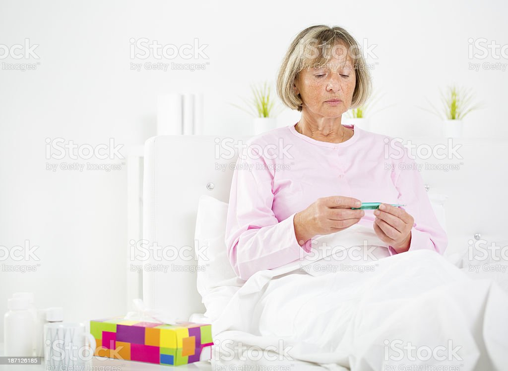 Sick Senior Woman Taking Her Temperature. royalty-free stock photo