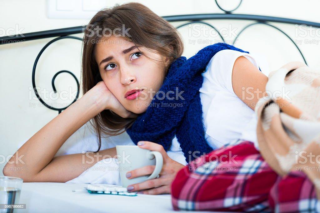 Sick teenage girl with hot tea and medication indoors stock photo