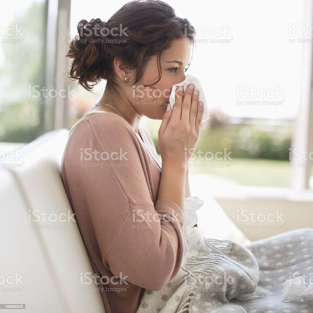 Sick woman blowing her nose royalty-free stock photo