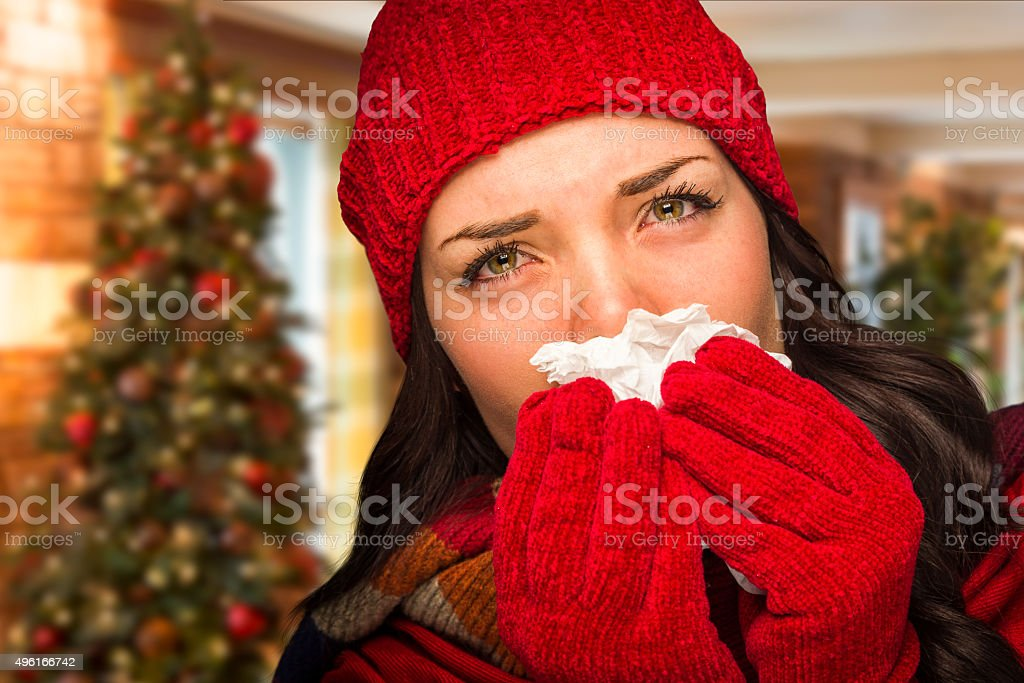 Sick Woman Blowing Her Nose With Tissue In Christmas Setting stock photo