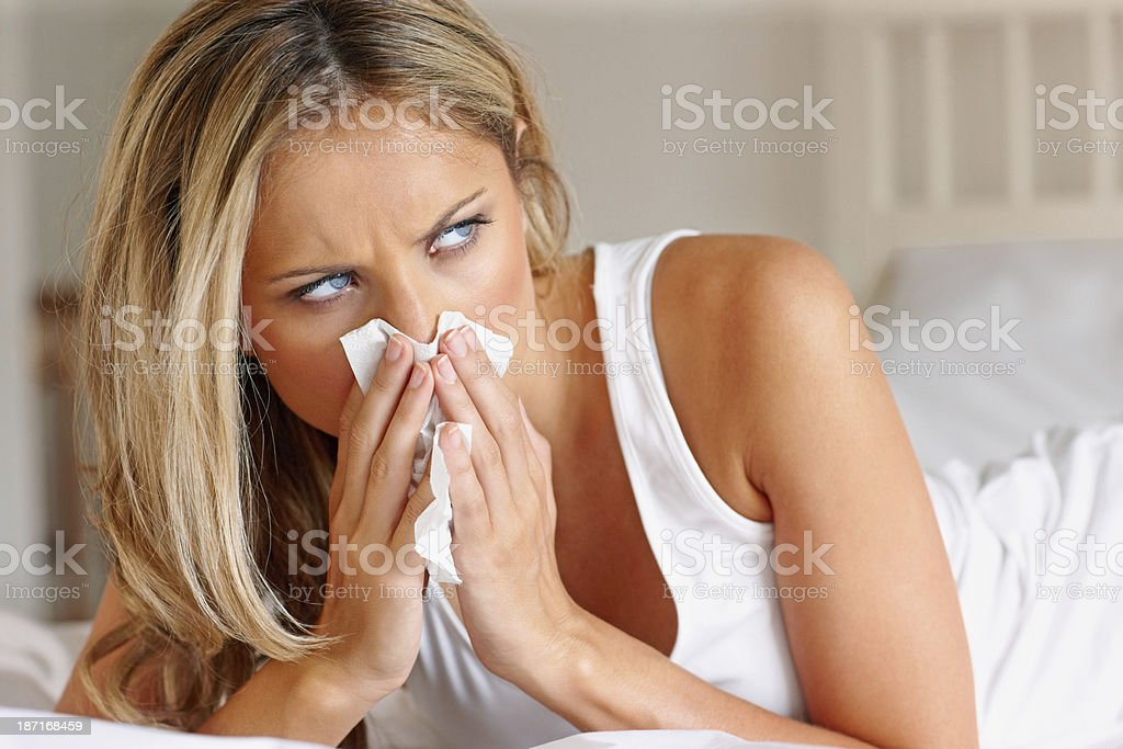 Sick woman blowing nose in tissue paper royalty-free stock photo