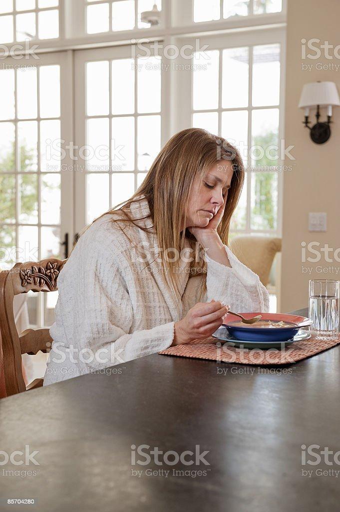 Sick Woman Having Soup at Kitchen Counter stock photo