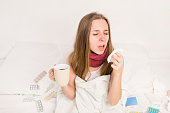 Sick woman holding cup of hot tea and yawning