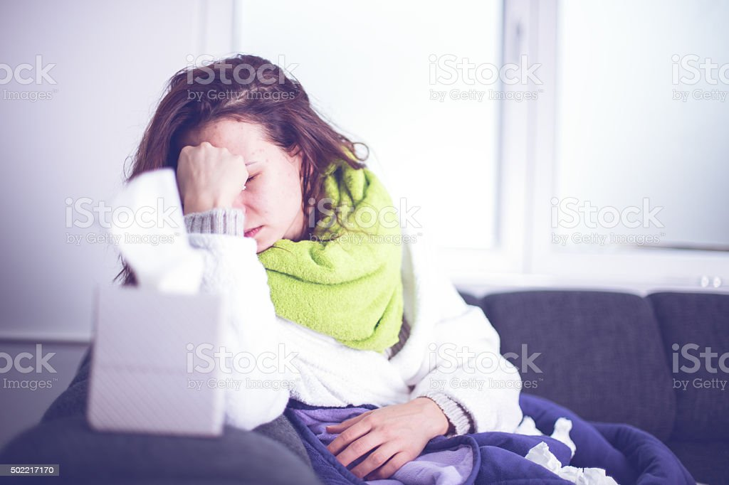 Sick woman in bed suffering flu headache stock photo