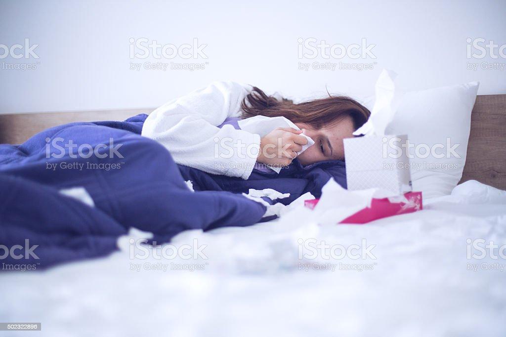 Sick woman in bed suffering flu headache stock photo
