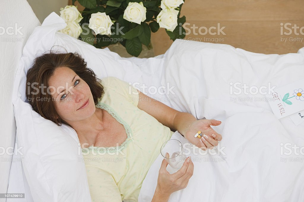 Sick woman laying in bed and taking pills with water royalty-free stock photo