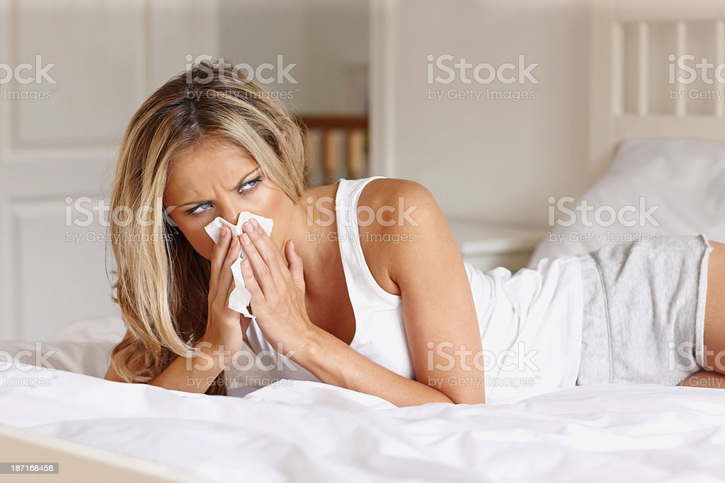 Sick woman on bed blowing nose royalty-free stock photo