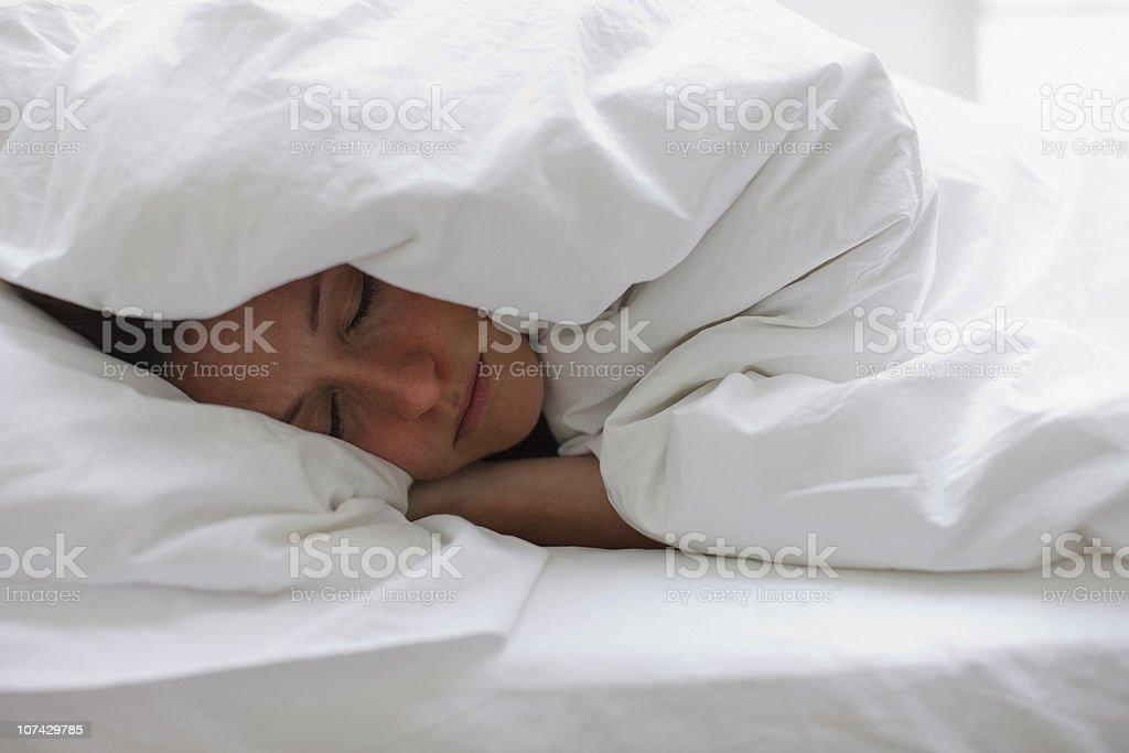 Sick woman sleeping in bed under blanket stock photo