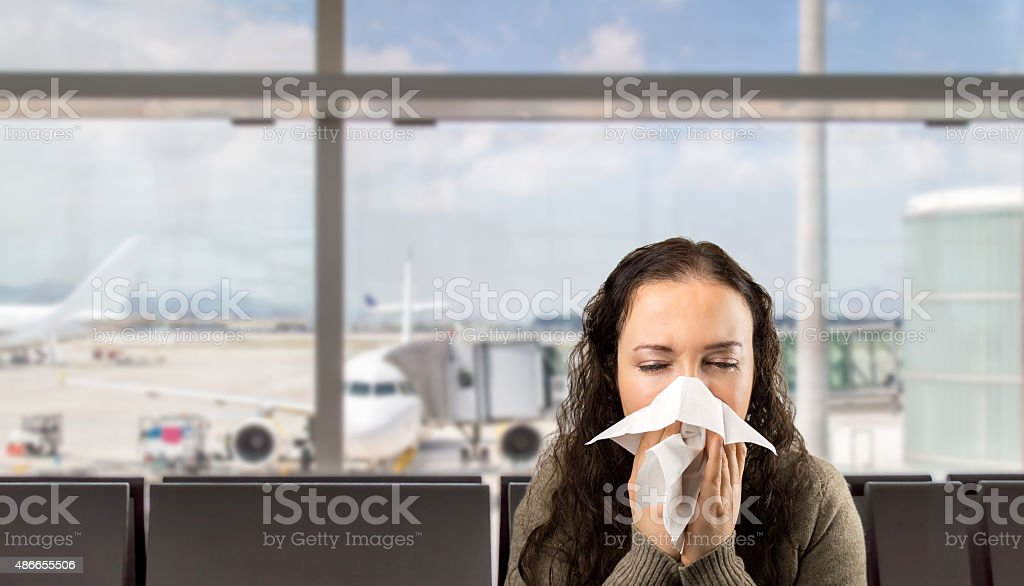 sick woman sneezing at the  airport stock photo