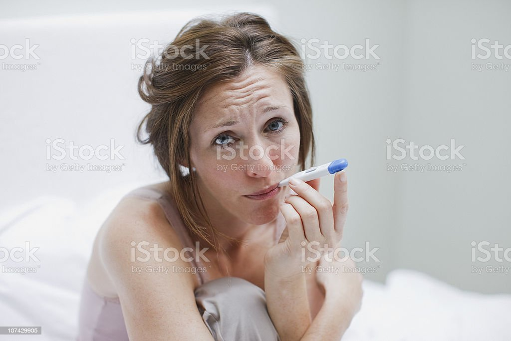 Sick woman taking temperature with digital thermometer royalty-free stock photo
